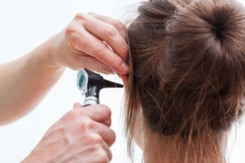 Looking into womans ear with otoscope
